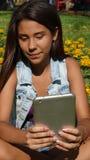 Tableta adolescente de la lectura de la muchacha Fotografía de archivo