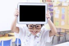 Tableta adorable de la demostración del pequeño niño en la escuela Imagen de archivo libre de regalías