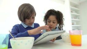 Tableta afroamericana de Digitaces del uso de los niños sobre el desayuno metrajes