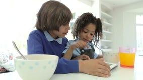 Tableta afroamericana de Digitaces del uso de los niños sobre el desayuno almacen de metraje de vídeo