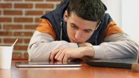 Tableta agujereada de las noticias de la lectura del estudiante, hombre joven que se sienta solamente en el café, depresión imagen de archivo