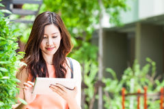 Tableta asiática del uso de la mujer en jardín foto de archivo libre de regalías