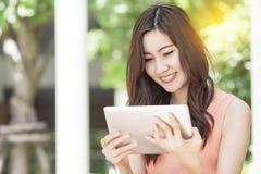 Tableta asiática del uso de la mujer en jardín foto de archivo