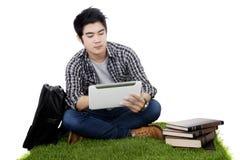 Tableta asiática masculina de las aplicaciones del estudiante en hierba imagen de archivo