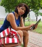 Tableta asiática moderna de las aplicaciones de la mujer en el parque imagen de archivo libre de regalías