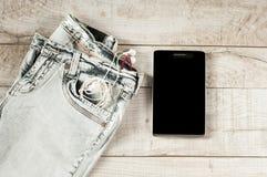 Tableta, auriculares, vaqueros Foto de archivo libre de regalías