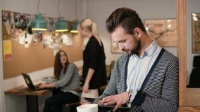 Tableta barbuda hermosa joven de la pantalla táctil de las aplicaciones del hombre y café de consumición en la oficina de lanzami metrajes
