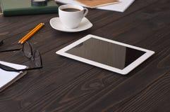 Tableta blanca en un escritorio de oficina de madera Foto de archivo libre de regalías
