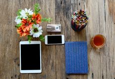 tableta, cámara del teléfono, lentes, cuaderno, caja de lápiz, flores Imágenes de archivo libres de regalías