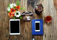 tableta, cámara del teléfono, lentes, cuaderno, caja de lápiz, flores fotografía de archivo