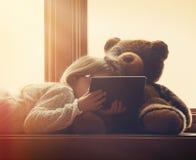 Tableta casual de la tenencia del niño con Teddy Bear en casa Fotos de archivo
