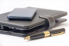 Tableta cerrada y pluma androide del teléfono móvil y del oro imagenes de archivo