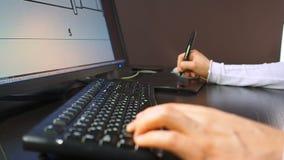 Tableta 27 Ciérrese para arriba de la mano de un ingeniero que corrige esquema en el sistema de cad, dimensión firmada en el moni metrajes