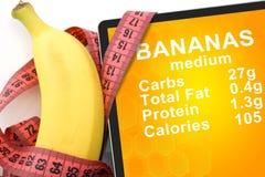Tableta con calorías en plátanos y cinta métrica Imagenes de archivo