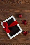 Tableta con el arco rojo, fondo de madera del regalo, concepto Christma Fotos de archivo