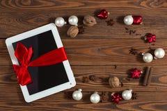Tableta con el arco rojo, fondo de madera del regalo, concepto Christma Imagenes de archivo
