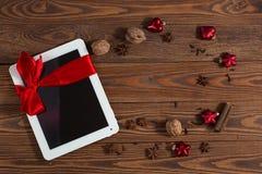 Tableta con el arco rojo, fondo de madera del regalo, concepto Christma Foto de archivo libre de regalías