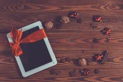 Tableta con el arco rojo, fondo de madera del regalo, concepto Christma Imágenes de archivo libres de regalías