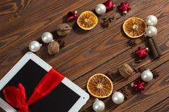 Tableta con el arco rojo, fondo de madera del regalo, concepto Christma Fotografía de archivo