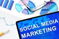 Tableta con el medios márketing, gráficos y vidrios sociales foto de archivo