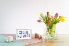Tableta con la escritura social de la red en el escritorio de madera con el CCB blanco Foto de archivo libre de regalías