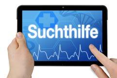 Tableta con la palabra alemana para el cuidado del apego - Suchthilfe imagen de archivo