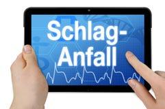 Tableta con la palabra alemana para el movimiento - Schlaganfall fotografía de archivo libre de regalías