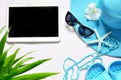 Tableta con la pantalla en blanco en la superficie blanca con los artículos de la playa, visión superior Fotos de archivo