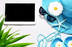 Tableta con la pantalla en blanco en la superficie blanca con los artículos de la playa, visión superior Imagenes de archivo