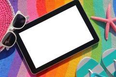 Tableta con la pantalla en blanco en la toalla de playa Fotografía de archivo libre de regalías
