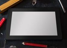 Tableta con la pantalla en blanco rodeada por las herramientas Foto de archivo