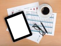 Tableta con la pantalla en blanco sobre los papeles con números y cartas Imagenes de archivo