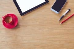Tableta con la pantalla en blanco, teléfono elegante en la tabla de madera Mofa del escritorio de oficina para arriba Visión desd Fotos de archivo libres de regalías