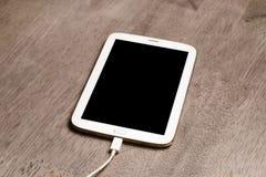 Tableta con la pantalla negra en el escritorio de madera Fotografía de archivo libre de regalías