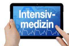 Tableta con la pantalla táctil y la palabra alemana para los cuidados intensivos - Intensivmedizin imágenes de archivo libres de regalías