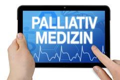 Tableta con la pantalla táctil y la palabra alemana para la medicina y el cuidado paliativos fotos de archivo libres de regalías