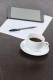 Tableta con la taza de café y de pluma en la tabla Fotografía de archivo