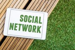 Tableta con las redes sociales que mienten en la madera y la hierba Foto de archivo libre de regalías