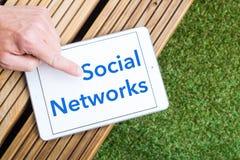 Tableta con las redes y los fingeres sociales el señalar Imagen de archivo libre de regalías