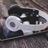 Tableta con los auriculares contra fondo de madera Imagen de archivo