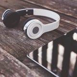 Tableta con los auriculares contra fondo de madera Foto de archivo libre de regalías