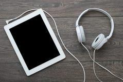 Tableta con los auriculares en superficie de madera Fotografía de archivo libre de regalías