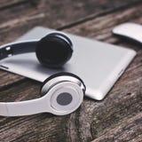 Tableta con los auriculares y el ratón contra backgro de madera fotos de archivo