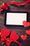 Tableta con los corazones rojos Imagenes de archivo