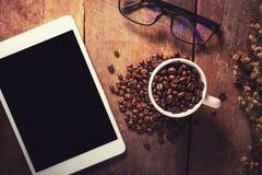 Tableta con los granos y los vidrios de café en la tabla de madera Fotos de archivo
