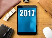 Tableta con número de 2017 años en la pantalla en la mesa de madera, Digital h Imagenes de archivo