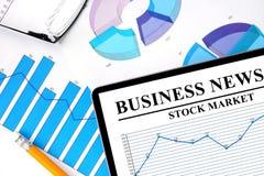 Tableta con noticias de negocio del mercado de acción Foto de archivo libre de regalías