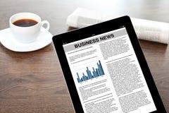 Tableta con noticias de negocio en una pantalla en una tabla  fotografía de archivo libre de regalías