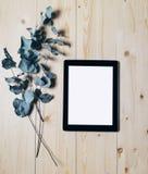 Tableta con un monitor limpio de la pantalla en blanco con una rama del eucalipto en un fondo de madera con el vert de madera nat fotografía de archivo
