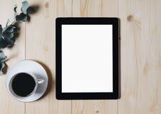 Tableta con un monitor limpio de la pantalla en blanco con una rama del eucalipto y una taza de caf? en un fondo de madera con ma imagenes de archivo